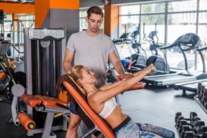 トレーニングをする女性と補助する男性