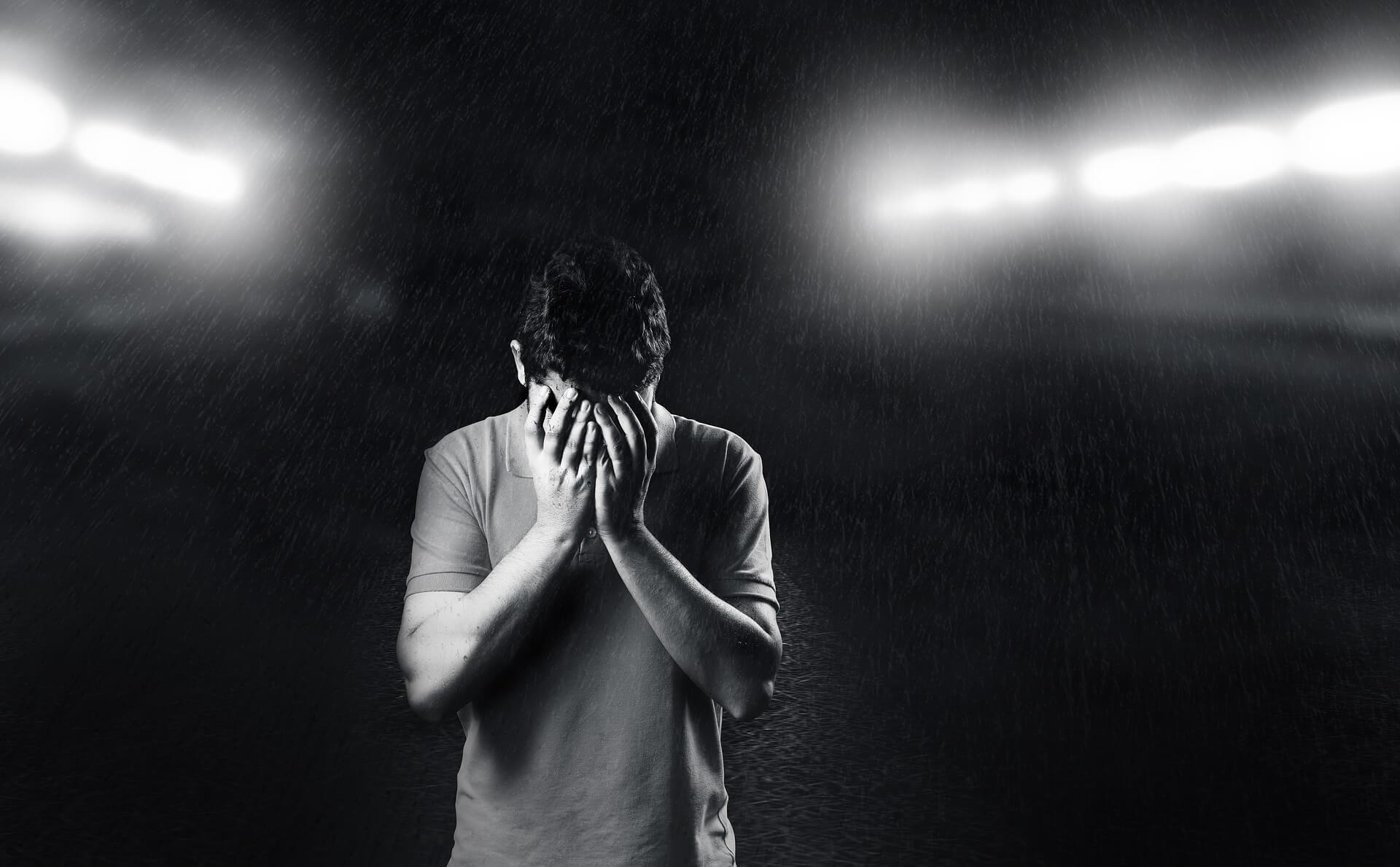 頭を抱えて悩む男性の画像