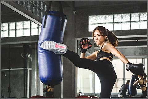 サンドバックを打って護身術を練習する女性