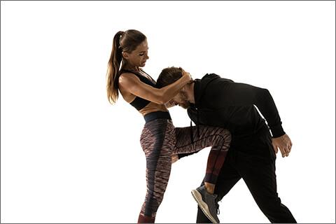男性に膝蹴りをしている女性